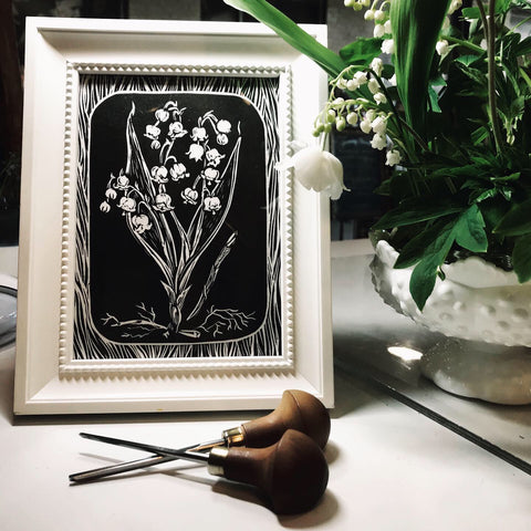 Framed lily of the valley original print with carving tools and May's flower