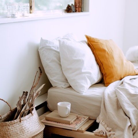 A cozy relaxing bed for sleeping with neutral tones on pillows and blankets