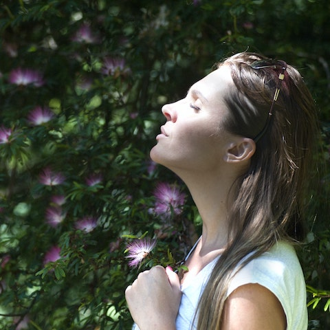 A woman with her eyes closed is enjoying sun on her face against a backdrop of green leaves and purple flowers