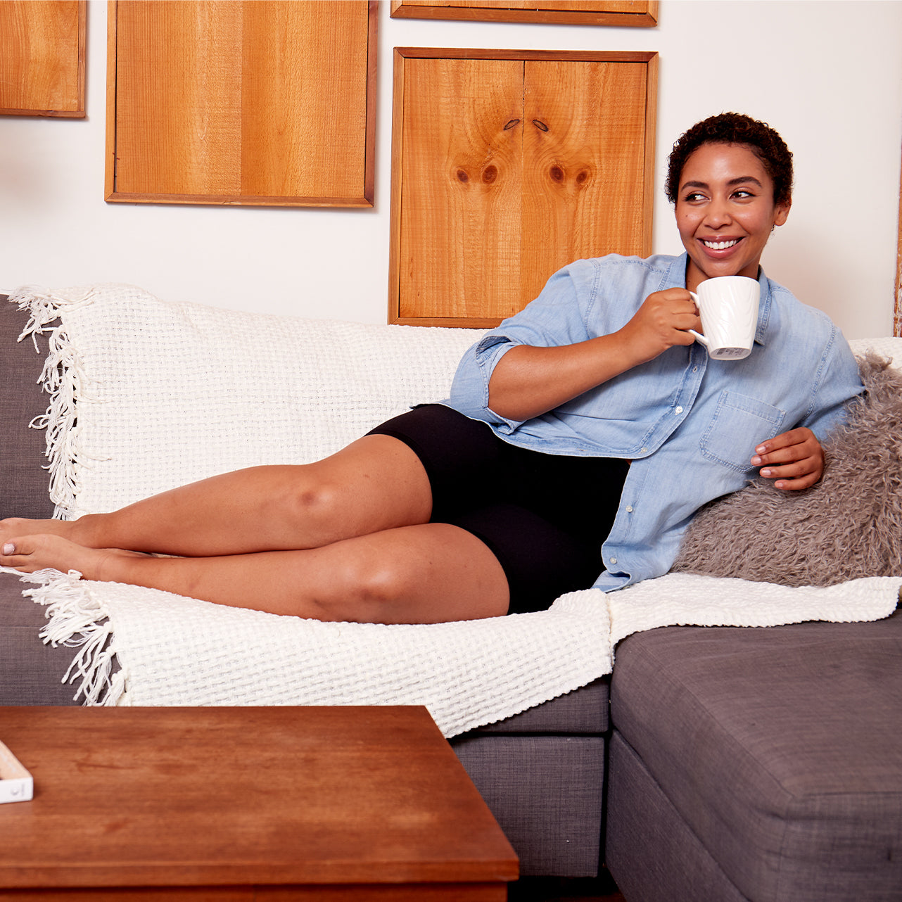 Woman wearing slip shorts drinking coffee