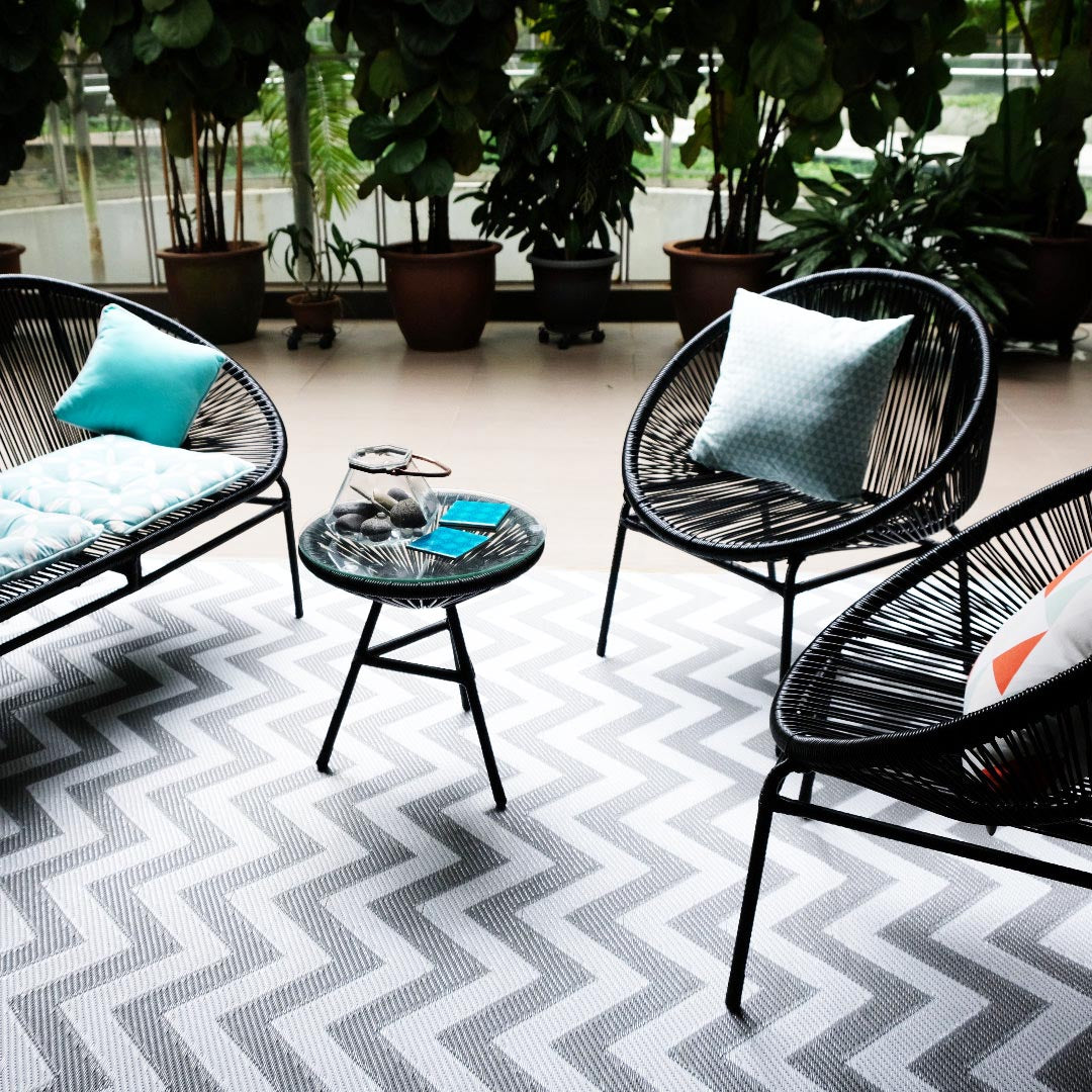 beautiful patio space with black outdoor furniture and rugs