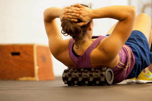 Woman on the floor using a foam roller on her back.