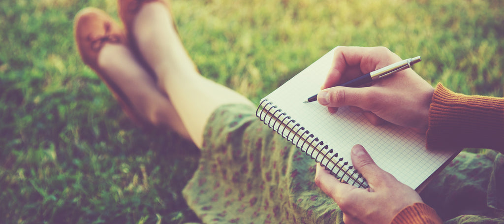 Woman sitting on grass with notebook on her lap, writing in it.