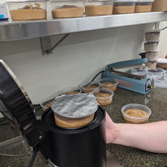 deli container seal machine with metal lid and hand pushing up sealed container from bottom of machine