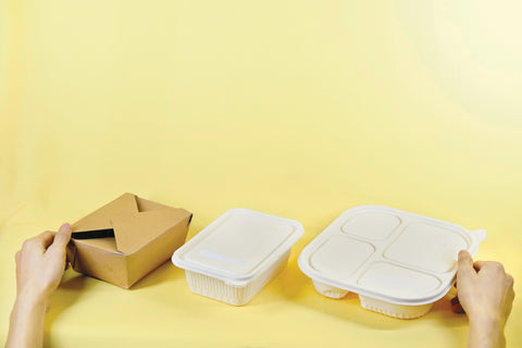 hands holding three types of take out (takeaway) packaging, one kraft brown, one made of paper, and one multi tray food server. tan background.