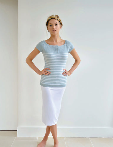 GIRL STANDING WITH HANDS ON HIPS AND LEGS CROSSED WEARING A KNIT SHORT SLEEVE BLUE TOP AND A WHITE SKIRT