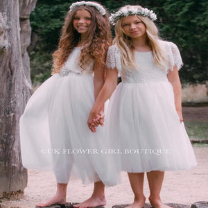 Girls wearing white flower girl dresses
