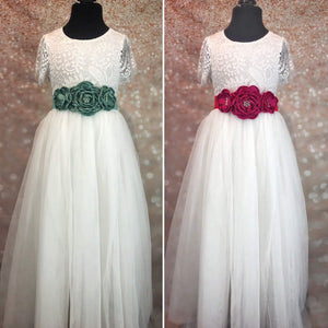 Green and red floral sashes on white dresses