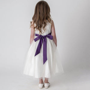 purple bow on back of girls white dress