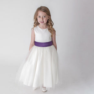 Girl in white party dress with purple sash