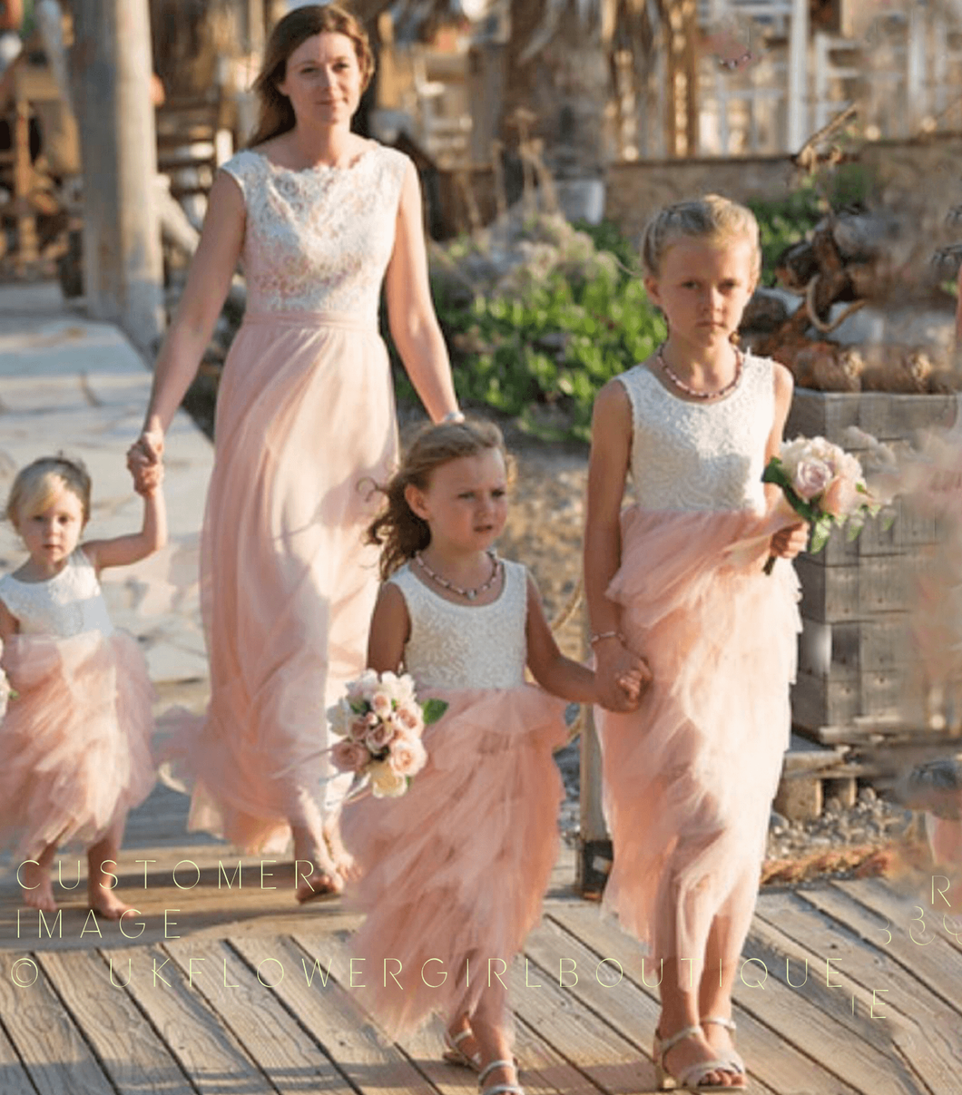 Girls wearing white and blush flower girls dresses for a wedding