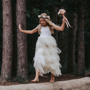 Girl holding bouquet and walking on log