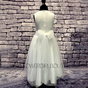 Isabella Flower Dress in with on a mannequin against a brick wall
