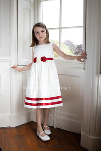 Young flower girl stood by window