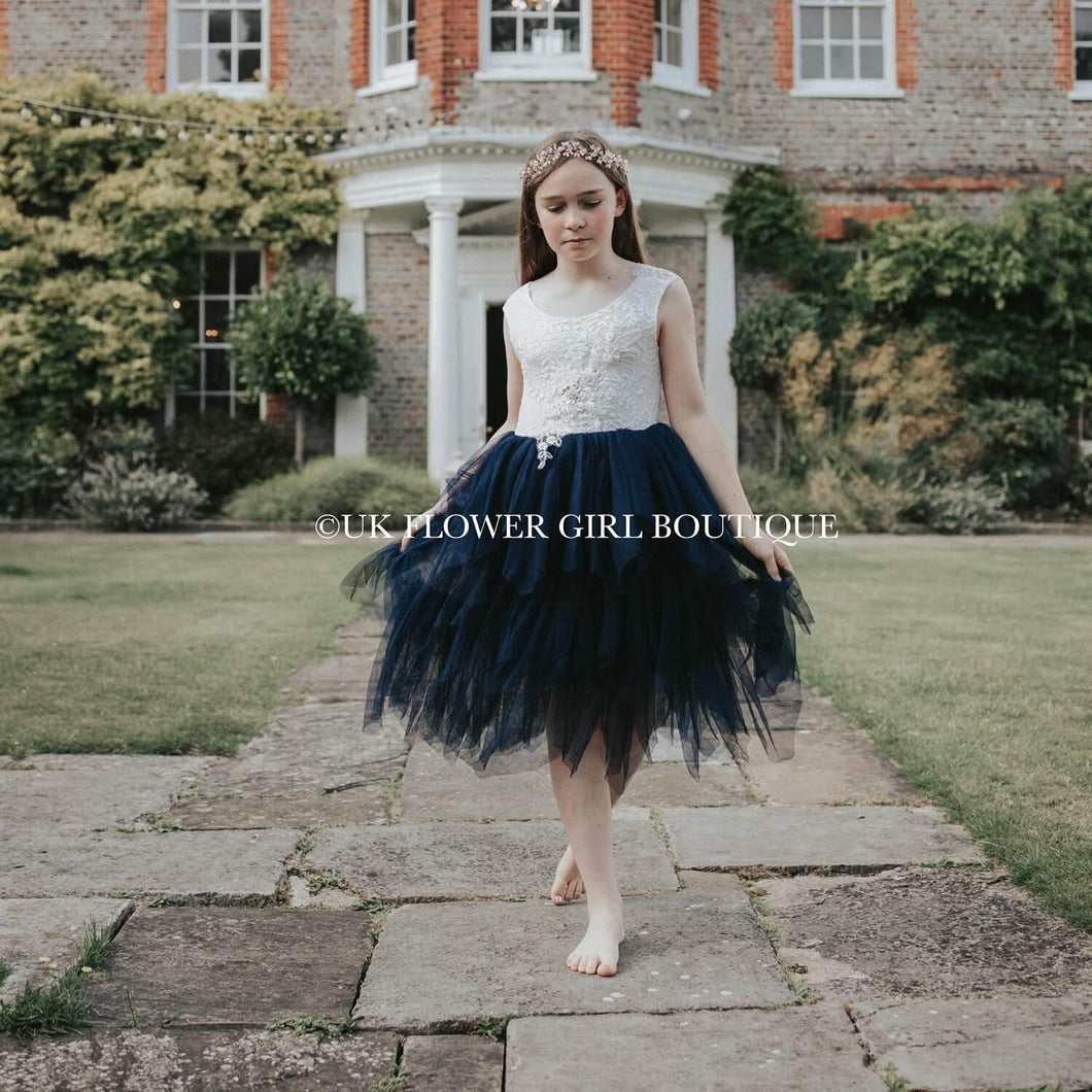 Girl wearing navy blue dress outside mansion
