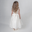 Girl wearing ivory party dress with bow on back
