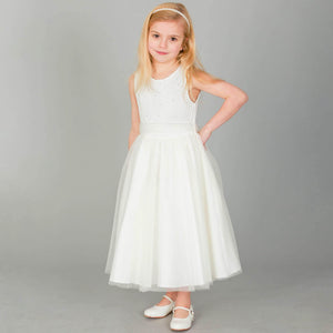 Blonde girl wearing ivory coloured party dress  and whit party shoes