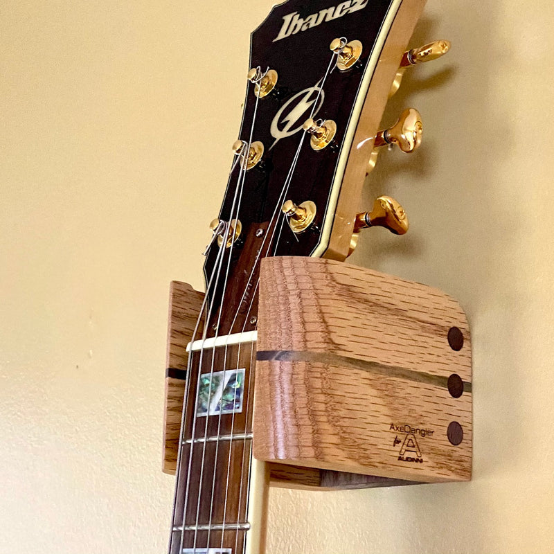 Close Up image of Audinni Guitar Wall Mount Cuff holding guitar
