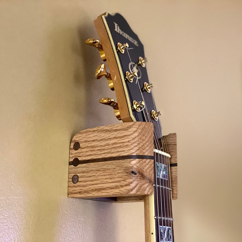 Side view of Audinni Guitar Wall Mount Cuff holding guitar