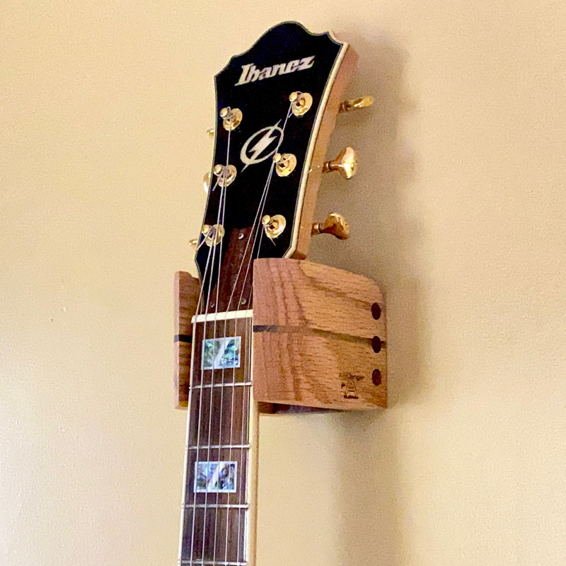 Audinni and Axe Dangler Guitar Wall Mount Cuff holding guitar in hardwood