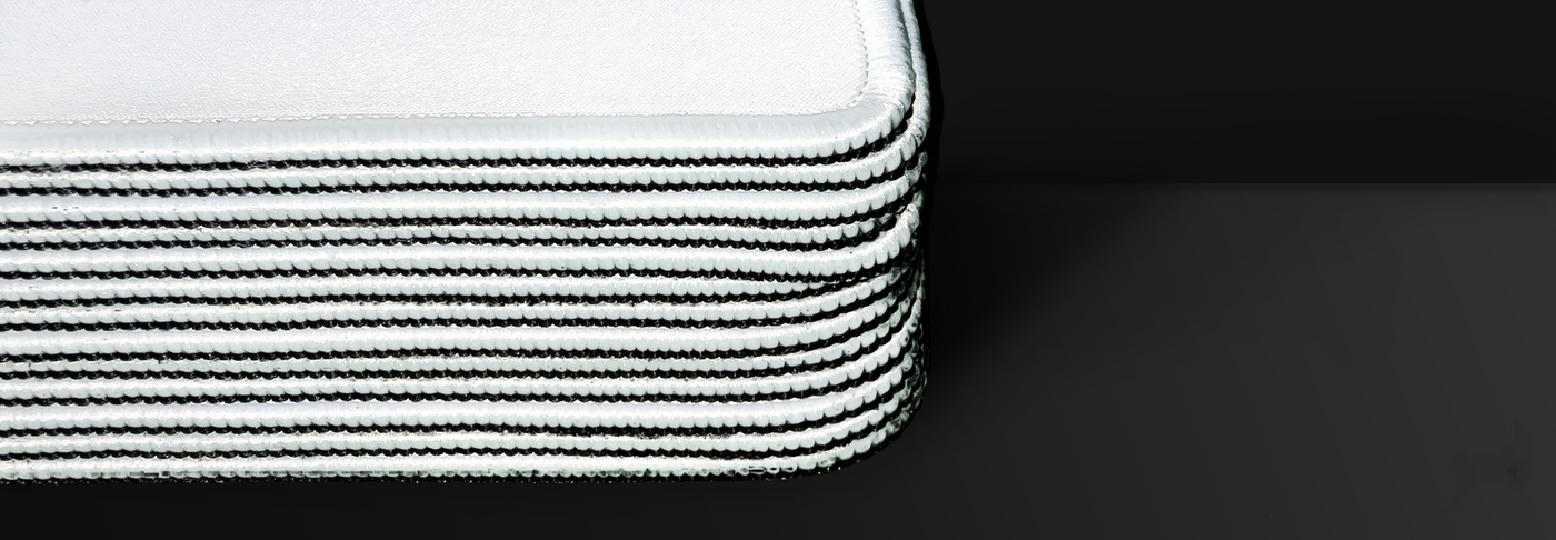 Close up image of the reinforced stitched edging of a stack of blank custom gaming mouse pads