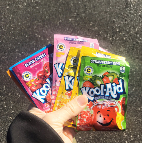 An image of a hand holding a variety of Kool-Aid packets. Part of a blog post by Amy Reader about how to dye yarn with Kool-Aid