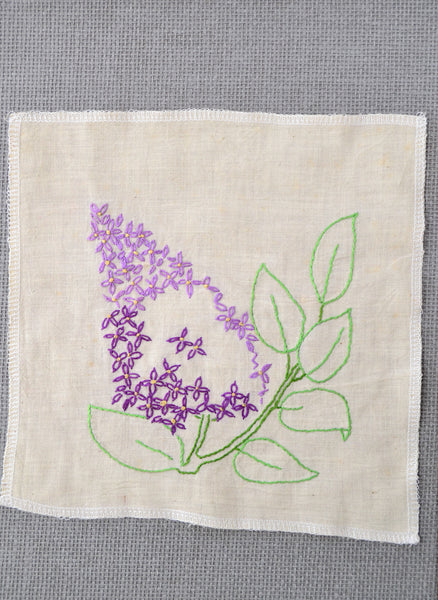 Lilac flower embroidery that was started by the grandmother of Amy Reader