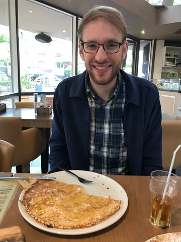 Adam eating a large Dutch pancake in Rotterdam, Netherlands - taken by Amy Reader Artist