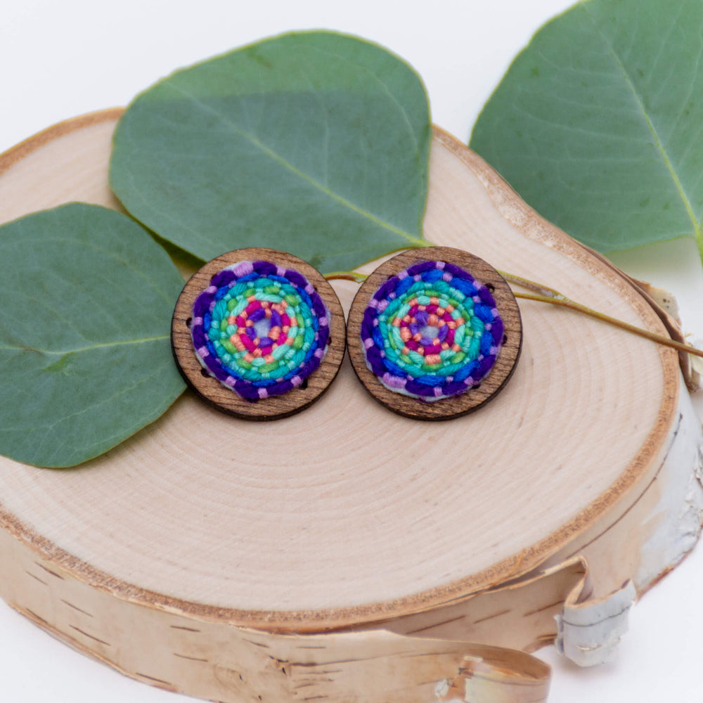 hand embroidered statement stud earrings stitched by Amy Reader of amyreaderartist.com the earrings are a reverse rainbow with purple on the outside mounted on wood,