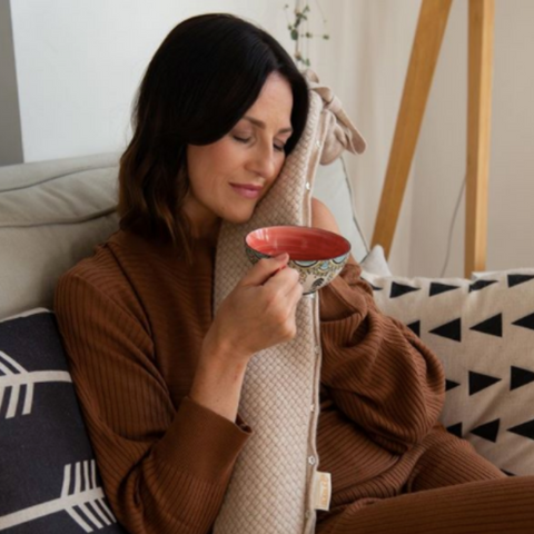 Woman enjoying her hot water bottle and a cup of tea