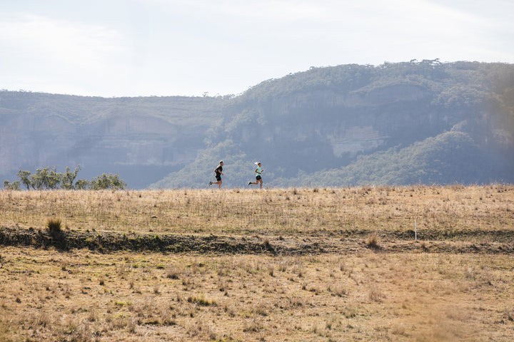 Two people running with mountains behind them