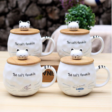 "Load image into Gallery viewer, Ceramic Mug with Lid & Spoon with Cat picture, and cat head on the lid that hands as a bobble handle to open it. This picture features all four variations of the mug with various pictures (fish variations) on it. All text on the mug reads: ""the cat's favourite""."