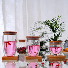 Load image into Gallery viewer, Double Walled Insulated Glass Cups With Bamboo Lid. This picture features all three size variations: 250ml, 350ml, and 450ml, all with some sweet, pink tea in them.