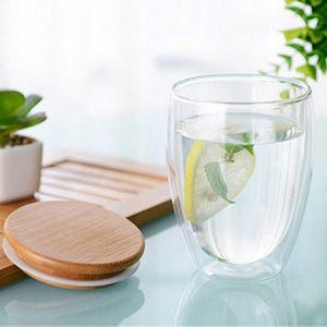 Double Walled Insulated Glass Cups With Bamboo Lid. This picture features the size variation: 350ml, with its bamboo lid to the left and water/lemon slice in the cup.