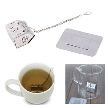 Load image into Gallery viewer, Home is where the Tea is, Stainless Steel Tea Infuser. This picture prominently shows the tea strainer, shaped as a house, with a the filter comprising of the windows and doors, as well as the word 'tea' spelt in capitals using holes in the roof.