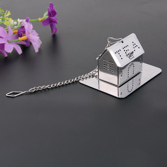 Home is where the Tea is, Stainless Steel Tea Infuser. This picture prominently shows the tea strainer, shaped as a house, with a the filter comprising of the windows and doors, as well as the word 'tea' spelt in capitals using holes in the roof.