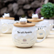 "Load image into Gallery viewer, Ceramic Mug with Lid & Spoon with Cat picture, and cat head on the lid that hands as a bobble handle to open it. This picture features a mug with a cat paw printed on it and text that reads: ""the cat's favourite""."
