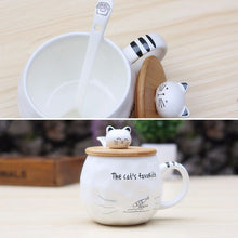 "Load image into Gallery viewer, Ceramic Mug with Lid & Spoon with Cat picture, and cat head on the lid that hands as a bobble handle to open it. This picture features a mug with a cat paw printed on it and text that reads: ""this cat's favourite"". As well as a view of the inside of the cup complete with matching spoon."