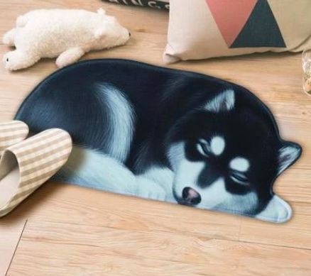 Image of a floor rug on a wooden floor in the shape of a sleeping Alaskan Malamute