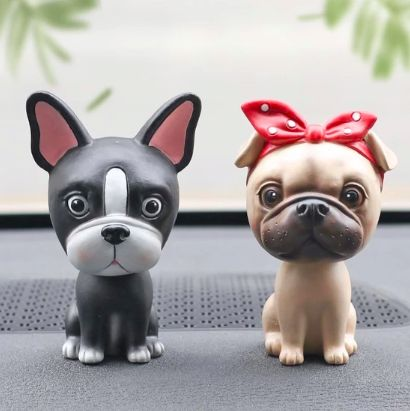 Image of two bobble heads on a car dashboard shaped like a Boston Terrier and a girl Pug