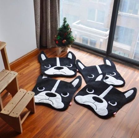 Image of four floor rugs lying on the floor shaped like cute Boston Terrier faces