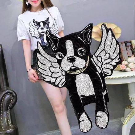 Image of a Boston Terrier with angel wings sew on patch for t shirt or jackets with a woman in the background wearing a t shirt with the same boston terrier sew on patch