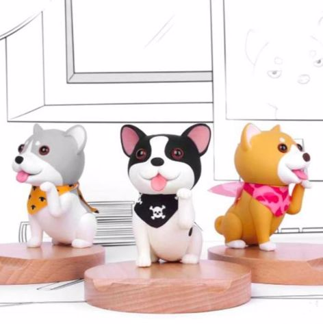 Image of three mobile phone holders, one shaped like a Boston Terrier and other two as a Husky and Shiba Inu
