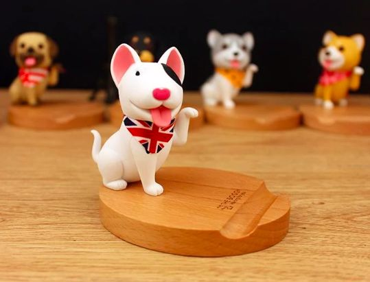 Image of a mobile phone holder on a wooden platform in the shape of a white Bull Terrier dog