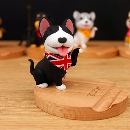 Image of a mobile phone holder on a wooden platform in the shape of a black Bull Terrier dog