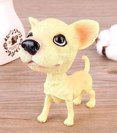 Image of a car bobble head in the shape of a standing Chihuahua dog on a wooden table