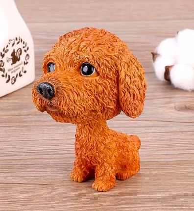 Image of a car bobble head lying on a table in a Cockapoo or Toy Poodle design