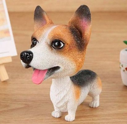 Image of a car bobble head which looks like a similing Corgi standing on a wooden tabletop