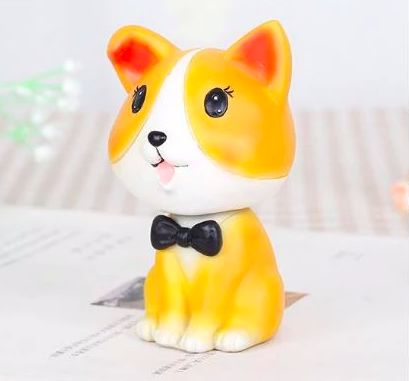Image of a cute Corgi themed car bobble head on a table top