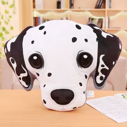 Image of a stuffed sofa cushion which looks like the face of a Dalmatian dog on a wooden table in a room